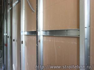 Возведение стены из гипсокартона. Профиля установлены через равные промежутки. С одной стороны гипсокартон уже закреплен.
