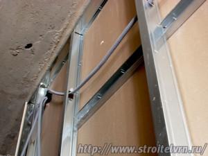 Электропроводка в изоляционной гофре протянута через отверстия профилей.